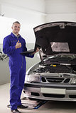 Smiling mechanic holding a computer with thumb up