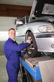 Mechanic standing while repairing a car wheel