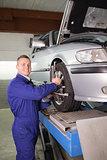 Mechanic standing while repairing a car wheel