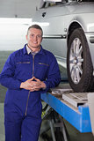 Front view of a smiling mechanic next to a car