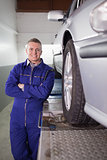 Front view of a mechanic smiling next to a car