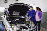 Mechanic showing a clipboard to a woman