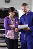 Mechanic showing the quotation to a woman