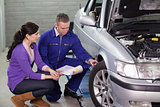 Mechanic showing the car wheel to a client