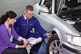 Mechanic showing the car wheel to a woman