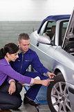 Mechanic touching the car wheel next to a woman