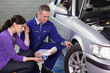 Mechanic looking at the car wheel next to a client