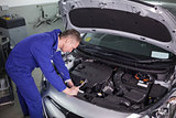 Concentrated mechanic repairing a car