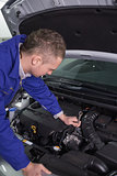 Mechanic repairing an engine with a spanner