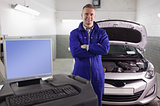 Mechanic next to a car and a computer