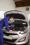 Concentrated mechanic looking at a car engine