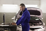 Mechanic standing while looking at a computer