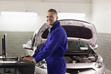 Smiling mechanic typing on a computer