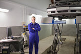 Smiling mechanic standing next to a car