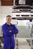 Smiling mechanic looking at camera next to a car