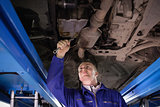 Concentrated mechanic repairing below of a car