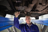 Smiling mechanic looking at camera while repairing a car