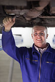 Smiling mechanic repairing the below of a car with a spanner