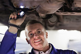 Mechanic looking at camera while holding a flashlight