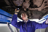 Mechanic looking the below of a car while holding a flashlight