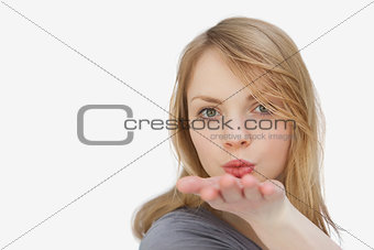 Blonde woman blowing on her hand