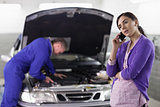 Woman calling next to a mechanic