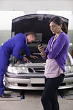 Woman looking a her mobile phone next to a mechanic