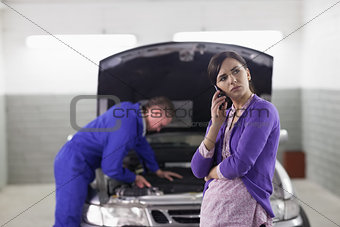 Client holding a mobile phone next to a car
