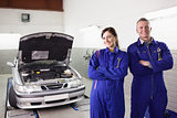 Smiling mechanics with arms crossed next to a car