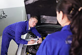 Mechanic leaning on a car looking at a colleague