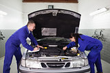 Mechanics examining a car engine