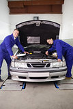 Mechanics smiling while leaning on a car