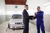 Mechanic giving car key while shaking hand to a client