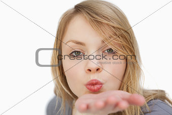 Blonde woman blowing on her palm