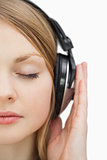 Close up of a woman with closed eyes listening music