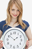 Woman holding a clock while looking at camera