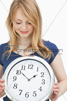 Blonde woman holding a clock while smiling