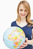 Woman holding a globe while looking at camera