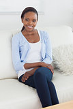 Black woman sitting on a sofa