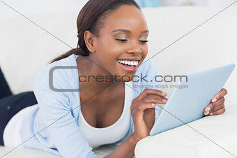 Black woman smiling while touching a tablet computer