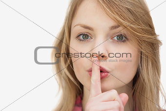 Woman putting a finger in front of her mouth