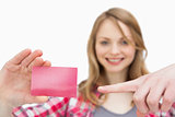 Woman holding a loyalty card while showing it with a finger