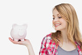 Woman looking at a piggy bank on her hand
