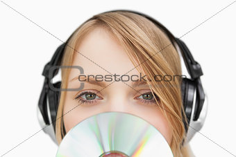 Close up of a woman with a cd in front of her face