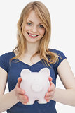 Blonde woman holding a piggy bank