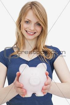 Blonde woman holding a piggy bank
