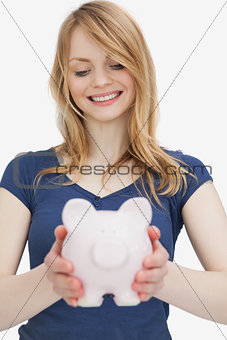 Blonde woman holding a piggy bank while looking it