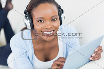 Black woman listening music while looking at camera