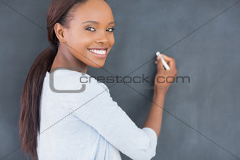 Black woman smiling while holding a chalk