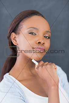Black woman holding a chalk while looking at camera
